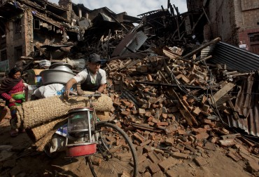 People walk past damage caused by Saturday's earthquake in Bhaktapur, on the outskirts of Kathmandu, Nepal, Monday, April 27, 2015. A strong magnitude earthquake shook Nepal's capital and the densely populated Kathmandu valley on Saturday devastating the region and leaving tens of thousands shell-shocked and sleeping in streets. (AP Photo/Niranjan Shrestha)