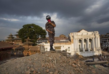 A Nepalese policeman stands atop of a rubble at Basantapur Durbar Square that was damaged in Saturday's earthquake in Kathmandu, Nepal, Sunday, April 26, 2015. The earthquake centered outside Kathmandu, the capital, was the worst to hit the South Asian nation in over 80 years. It destroyed swaths of the oldest neighborhoods of Kathmandu, and was strong enough to be felt all across parts of India, Bangladesh, China's region of Tibet and Pakistan.(AP Photo/Bernat Armangue)